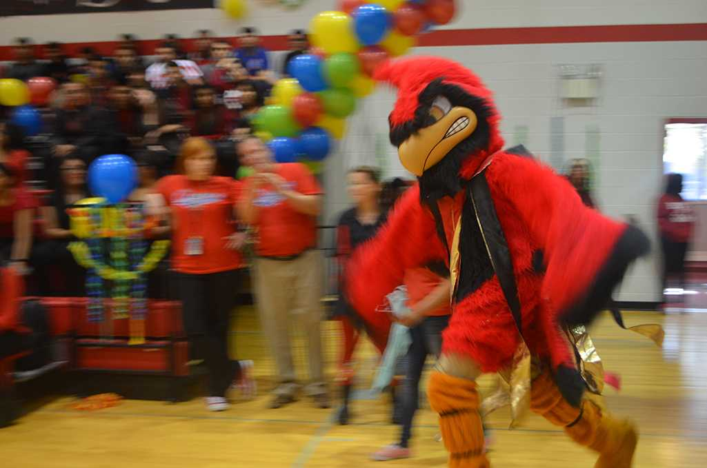 Junior Samuel Ferguson enters the gym at the homecoming pep rally as the school mascot flappng his wings in order to pump up the crowd.